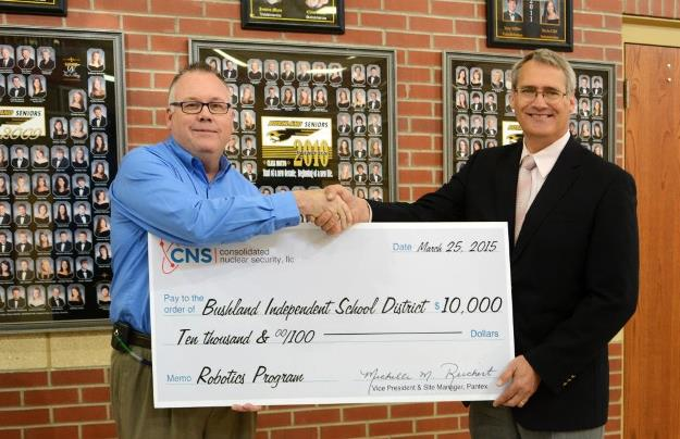 Joe Papp, CNS Director of Mission Engineering, presents the 0,000 donation to Don Wood, Bushland ISD Superintendent, to kick off the district's robotics program.